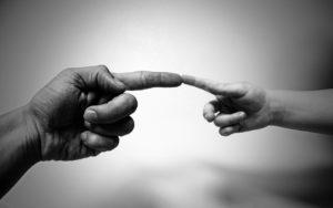 אצבעות של ילד ומבוגר נוגעות אחת בשניה